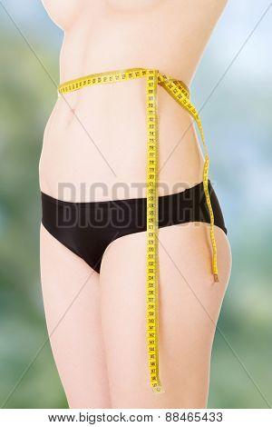 Slim woman measuring waist line.