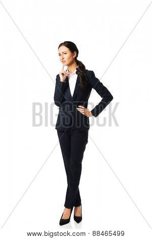 Full length thoughtful businesswoman with a finger under chin.