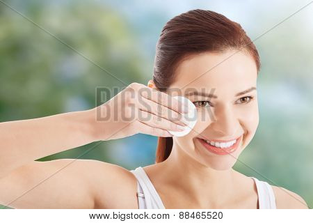Woman removing makeup with cotton pad.