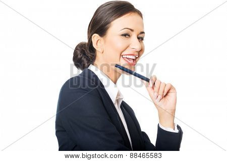 Portrait of businesswoman holding pen under chin, looking at the camera.