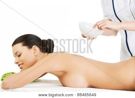 Young woman getting clay mask on her back.