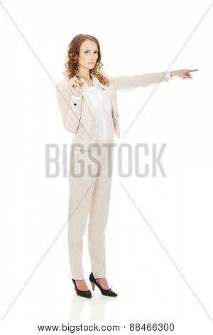Attractive serious businesswoman pointing her finger.