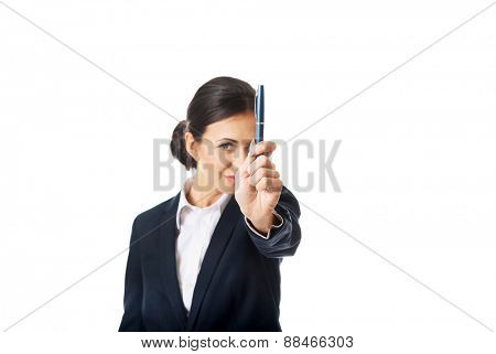 Photo of businesswoman pointing by a pen, looking at the camera.