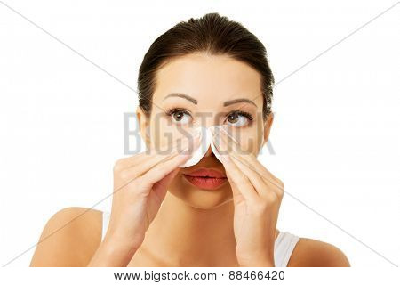 Young beautiful woman removing make up.