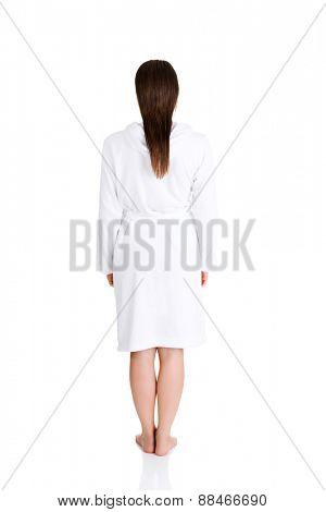 Back view woman standing, wearing bathrobe.