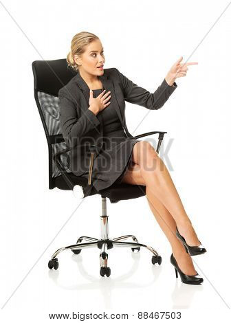 Businesswoman sitting on a chair and showing empty space.