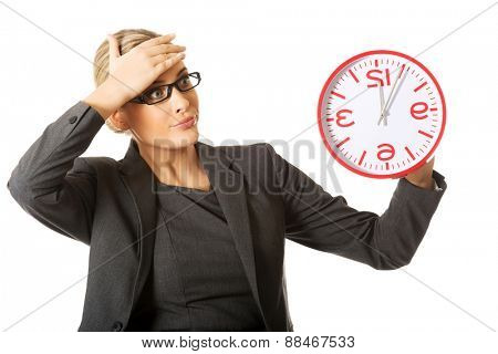 Surprised businesswoman holding a big clock.