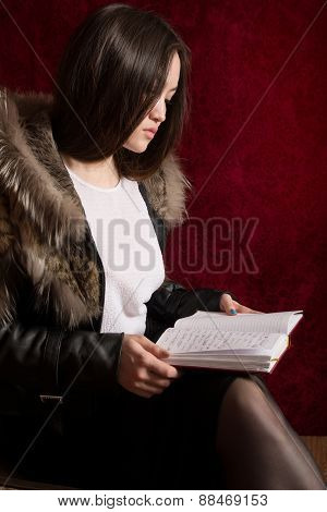 Young Girl In A Fur Coat Sitting Back And Reading The Manuscript.