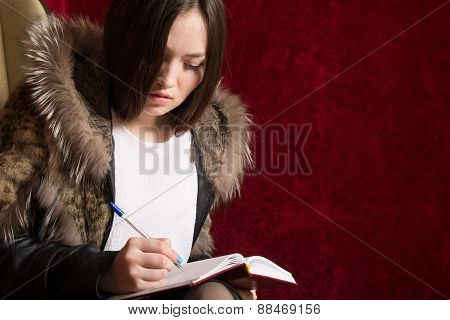 Young Girl In A Fur Coat Sits Back And Takes Notes