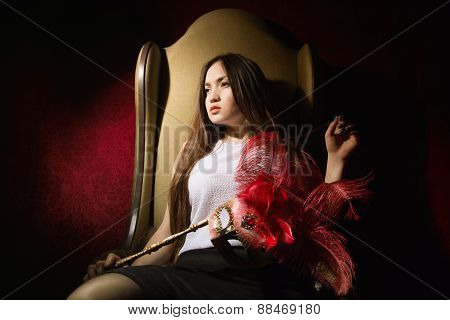 Asian Girl Sitting In A Chair Thoughtfully Looks Away.