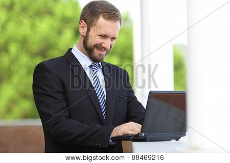 Happy Business Man Working Browsing Internet In A Laptop Outdoor