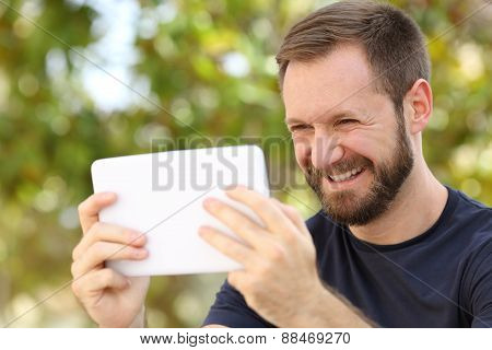 Happy Man Watching Videos In A Ereader Tablet