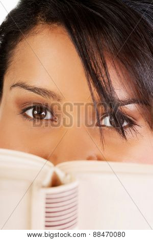 Young mulato woman hiding herself behind a book.