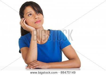 Portrait of thoughtful woman sitting at the desk.