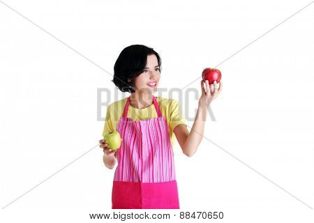 Woman in kitchen apron holding apples.