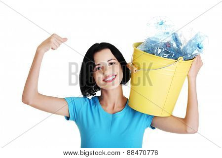 Happy woman holding bucket of plastic rubbish.