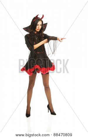 Full length woman wearing devil clothes pointing to the corner.
