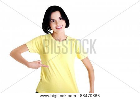 Portrait of young woman pointing on shirt.