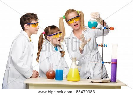 Teens and teacher of chemistry at  lesson making experiments