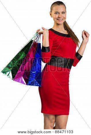 Half-turned woman handing bags