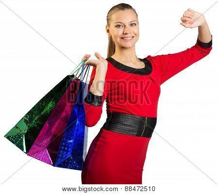 Woman with teeth smile handing three bags