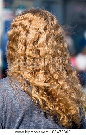 woman with long blond hair, a symbol of femininity, anonymity
