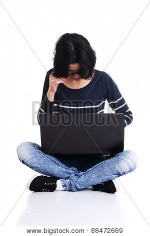 Pensive woman sitting cross-legged with laptop.