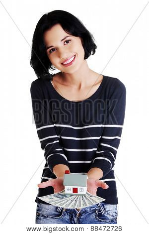 Happy woman holding a house model and dollar bills.