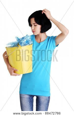Pensive woman holding bucket of plastic rubbish.