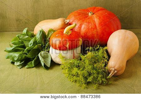 Different Pumpkins And Foliage On A Green Background