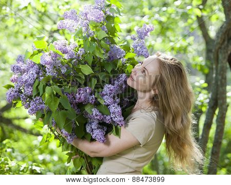 happy young woman in park with a big bouquet of a lilac