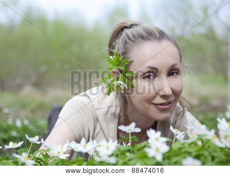 The young beautiful woman in the field of blossoming snowdrops in the early spring