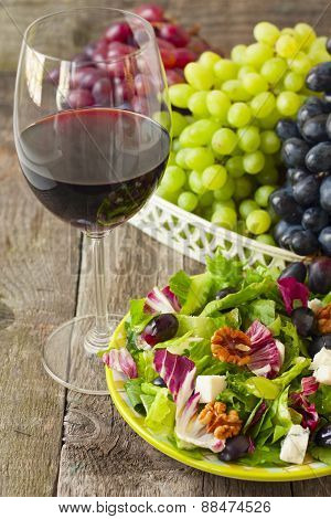 A Glass Of Wine And Salad With Grapes, Herbs, Walnuts And Blue Cheese On Wooden Background