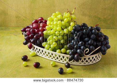 Clusters Of Dark, Red And Green Grapes On A White Tray On A Green Wooden Background