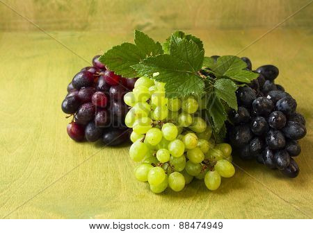 Clusters Of Dark, Red And Green Grapes On A  Green  Background