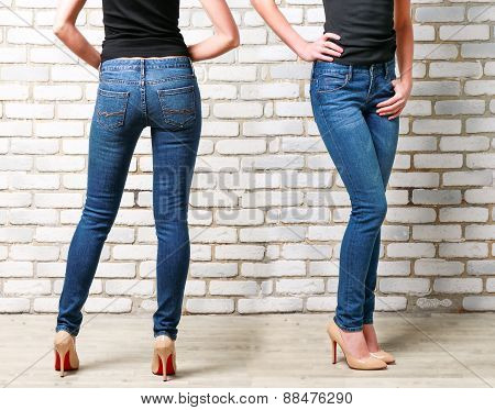 Woman legs in jeans on brick wall background
