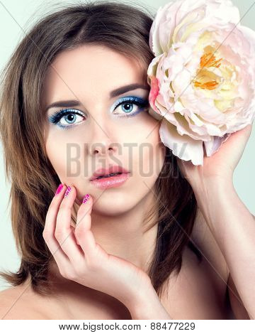 Beautiful Young Woman with Blue Eyes, Long Lashes and Pink nails. Flower in her Hair.
