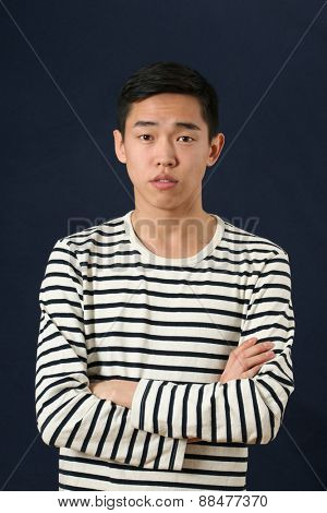 Young Asian man with crossed hands looking at camera
