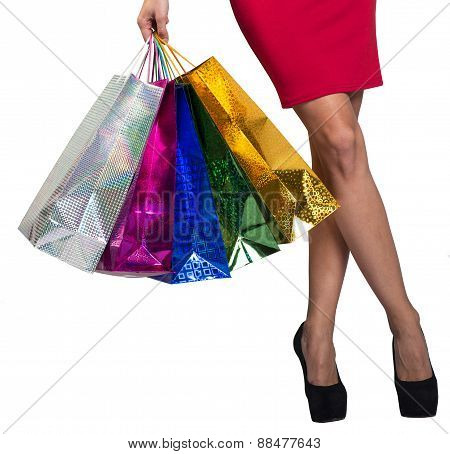 Womans crossed legs and hand holding bags