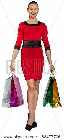 Laughing woman handing bags with right leg forward