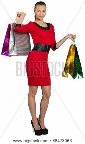 Half turned smiling woman handing bags up