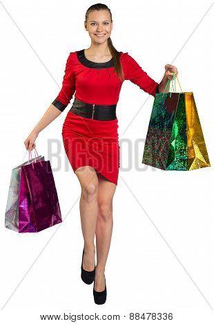Walking woman handing four bags up