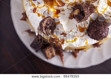 Air View Of Meringue Cake With Chocolate, Caramel, And Filled Chocolates