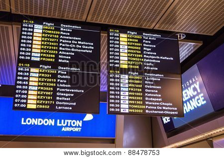 LONDON, UNITED KINGDOM - April 12, 2015: Airport departure board screen at Luton airport in London, UK
