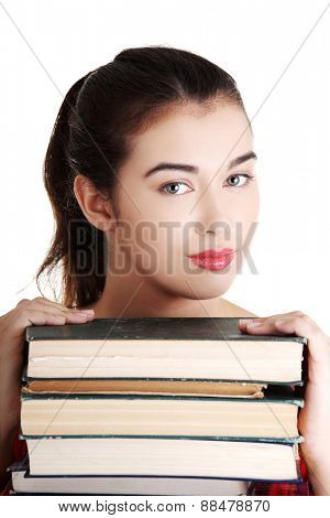 Young student woman eith stack of books.