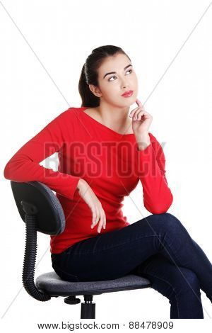 Young pensive student woman siting on armchair.