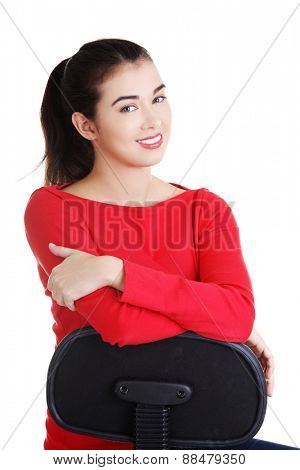 Young student woman siting on armchair.