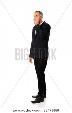 Full length businessman covering mouth.