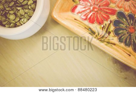 Yellow Porcelain Tablemat And Dried Pease On A Pastel Green Background