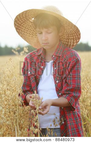 Portrait Of Teenage Ranch Boy Holding Oat Seeds With Outer Shells In Cupped Palms With Sun Flare